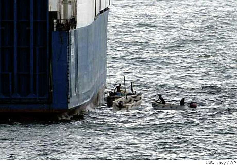 "** FILE ** In this picture released by U.S. Navy, Sunday,  Sept. 28, 2008, Somali pirates in small boats are seen alongside the hijacked ""Faina"". Armed pirates aboard fast-moving skiffs have increasingly turned the shipping lanes off Somalia into a lucrative hunting grounds: commandeering vessels large and small and leaving the world's maritime powers frustrated about how to stop the seafaring bandits. Now, however, momentum is growing for coordinated international action to back up the sharp response after the stunning seizure late last month of a Ukrainian cargo ship laden with tanks and heavy weaponry  as the pirates quickly found themselves encircled by U.S. warships and receiving only silence to their demands for millions of dollars in ransom. (AP Photo/U.S. Navy) Photo: U.S. Navy, AP"