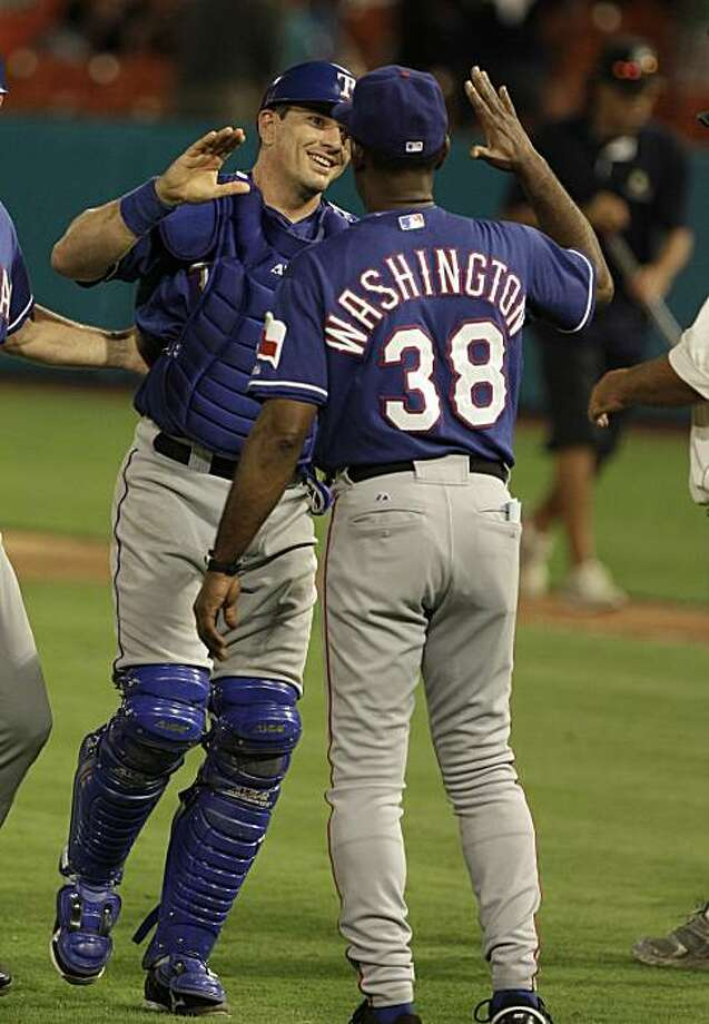 Texas Rangers catcher Matt Treanor, left, is congratulated by manager Ron Washington (38) after the Rangers defeated the Florida Marlins 3-2 in a baseball game in Miami on Tuesday, June 15, 2010. Treanor his a two-run triple in the ninth inning. Photo: Lynne Sladky, AP