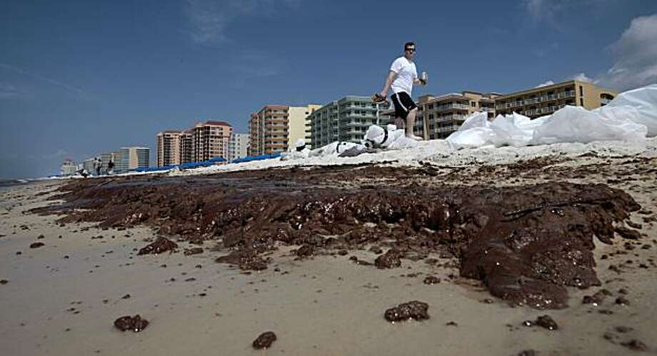 Jeb Harrison of Birmingham, Ala., walks along the beach looking at long lines of crude oil from the Deepwater Horizon oil spill in Orange Beach, Ala., Saturday, June 12, 2010.  Large amounts of the oil battered the Alabama coast, leaving deposits of the slick mess some 4 inches thick on the beach in some parts. Photo: Dave Martin, AP