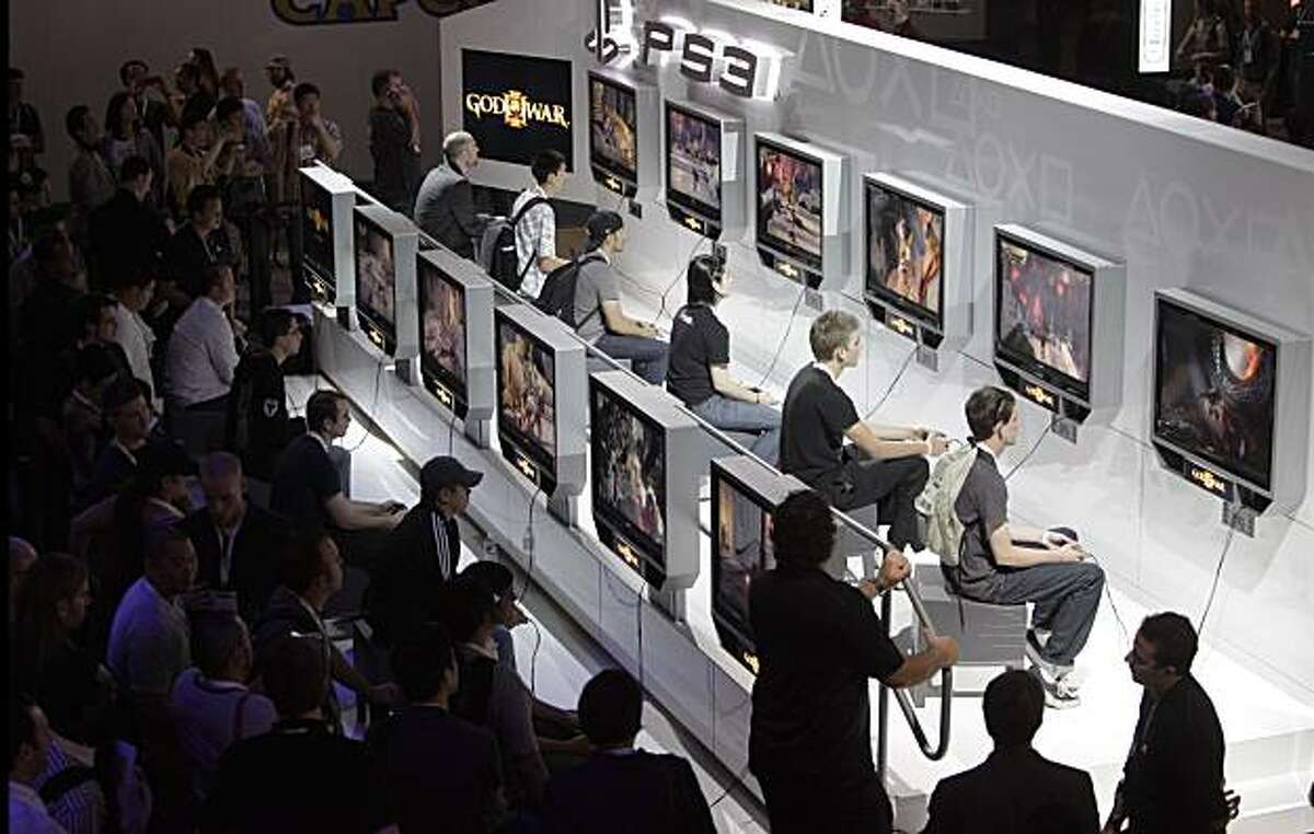 FILE - In this June 3, 2009 file photo, show attendees play the video game God of War III at the E3 Expo in Los Angeles. (AP Photo/Jae C. Hong, file)
