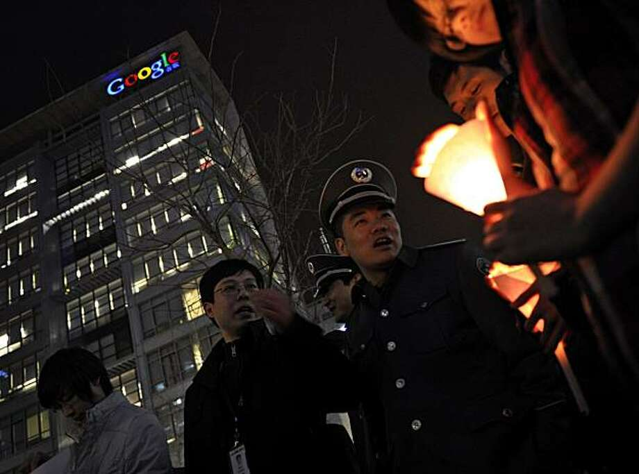Security officers try to stop people lighting candles outside the Google China headquarters in Beijing Tuesday, March 23, 2010. Google Inc. stopped censoring the Internet for China by shifting its search engine off the mainland Monday but said it will maintain other operations in the country. The maneuver attempts to balance Google's disdain for China's Internet rules with the company's desire to profit from an explosively growing market. Photo: Andy Wong, AP