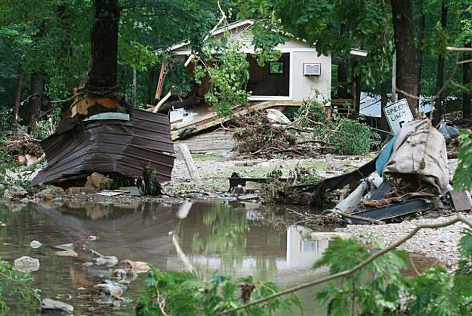 ** CORRECTS TO REVERT TO ORIGINAL LOCATION ** Damage to structures at the Albert Pike Campground in Caddo Gap, Ark. is seen Friday, June 11, 2010, after a flash flood of the Little Missouri River. At least 16 people were killed, and dozens more missing and feared dead. (AP Photo/The Arkansas Democrat-Gazette, Rick McFarland) MORNING NEWS OF NORTHWEST ARKANSAS OUT; PINE BLUFF COMMERCIAL OUT; ARKANSAS TIMES OUT; ARKANSAS BUSINESS OUT Photo: Rick McFarland, Arkansas Democrat-Gazette