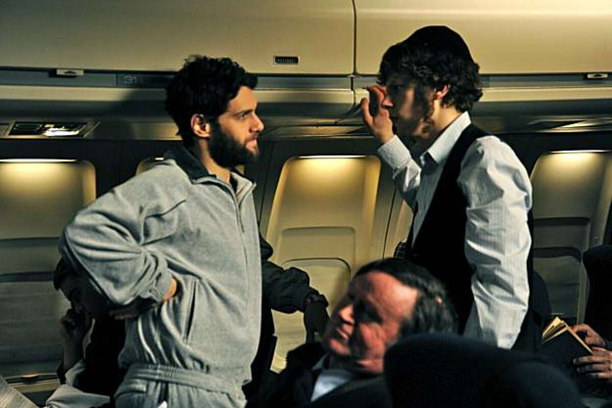 In this film publicity image released by First Independent Films, Jesse Eisenberg, right, and Justin Bartha are shown in a scene from,