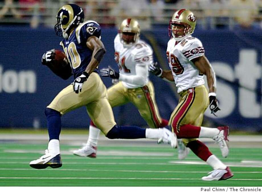 Rams WR Issac Bruce tries to turn the corner on 49ers defenders Ahmed Plummer (29) and Zack Bronson (background). First quarter of San Francisco 49ers vs. St. Louis Rams at the Edward Jones Dome in St. Louis on 9/14/03. PAUL CHINN / The Chronicle Photo: Paul Chinn, The Chronicle