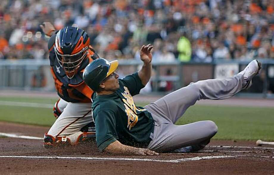 San Francisco Giants catcher Bengie Molina tags Oakland Athletics Cliff Pennington out at home in the first inning, Friday June 11, 2010, in San Francisco, Calif. Photo: Lacy Atkins, The Chronicle