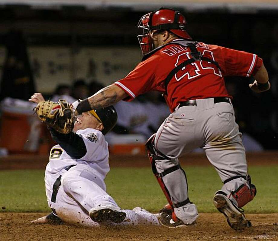 Oakland Athletics' Gabe Gross, left, slides safely into home around the tag of Los Angeles Angels catcher Mike Napoli during the seventh inning of a baseball game, Tuesday, June 8, 2010 in Oakland, Calif.  The Athletics beat the Angels 10-1. Photo: George Nikitin, AP