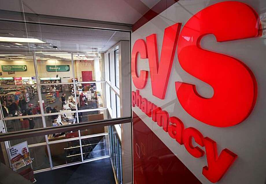 In this Nov. 3, 2009 photo, a CVS pharmacy sign is seen opposite the interior of one of the CVS locations, in Providence, R.I. CVS Caremark Corp. said Thursday, Nov. 5, 2009, its third-quarter profit jumped 39 percent on a boost from pharmacy benefits services and drugstore sales. (AP Photo/Steven Senne) Photo: Steven Senne, AP