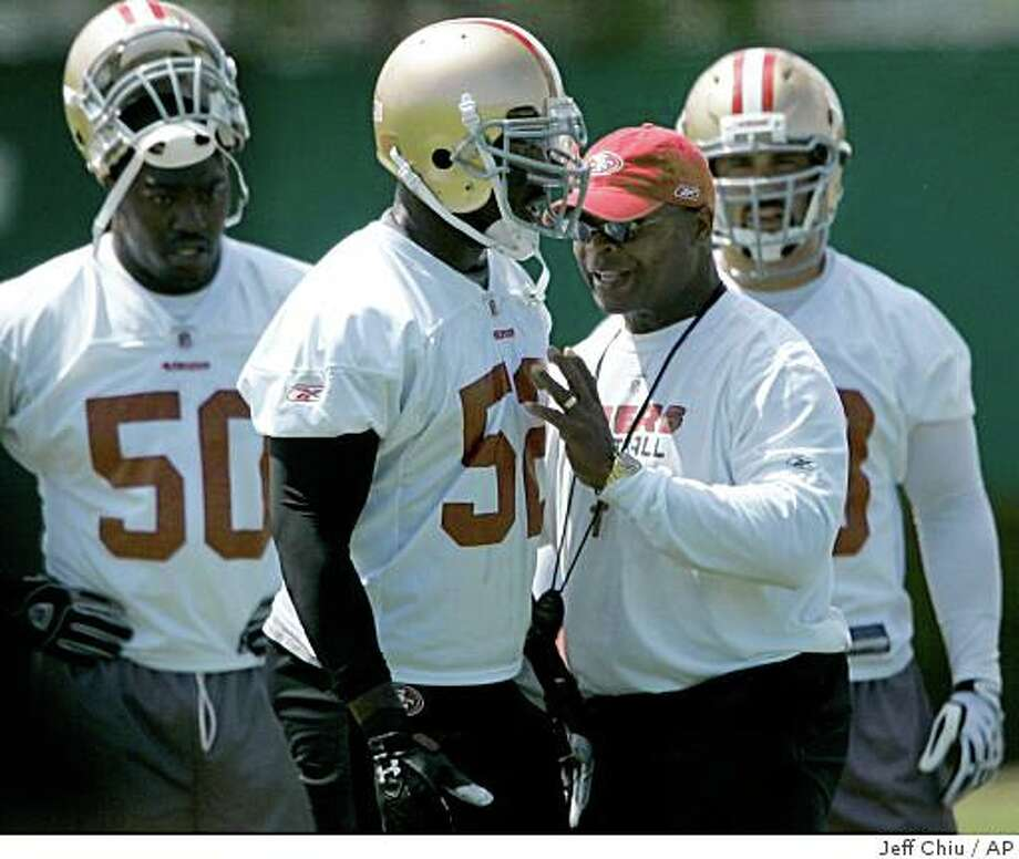 San Francisco 49ers head coach Mike Singletary, second from right, gives instruction to linebacker Patrick Willis, second from left, during 49ers NFL football mini-camp at 49ers headquarters in Santa Clara, Calif., Saturday, June 6, 2009. (AP Photo/Jeff Chiu) Photo: Jeff Chiu, AP