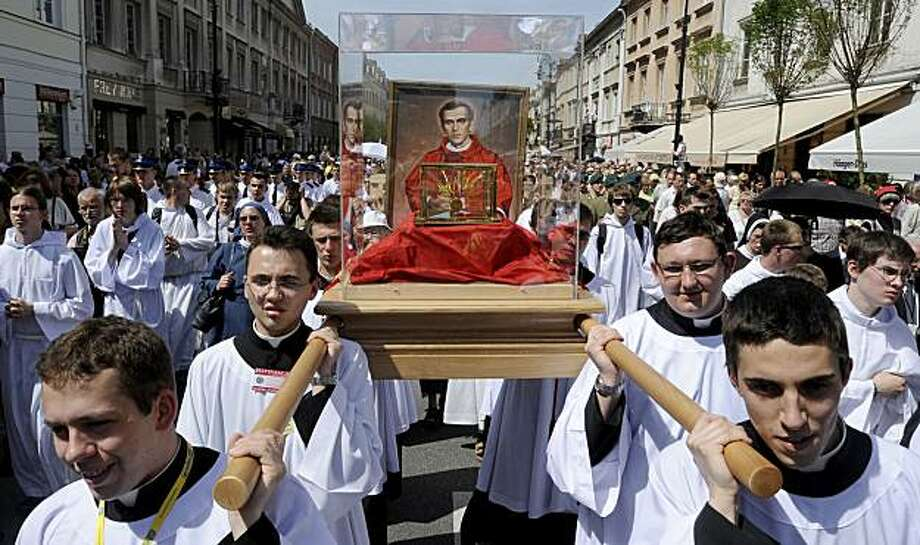 Young priests carry the relics of beatified Jerzy Popieluszko during a procession following the beatification mass for him in Warsaw, Poland, Sunday, June 6, 2010. Jerzy Popieluszko, a charismatic priest was tortured and killed in 1984 by communist Poland's secret police for supporting Lech Walesa's Solidarity movement. Photo: Alik Keplicz, AP
