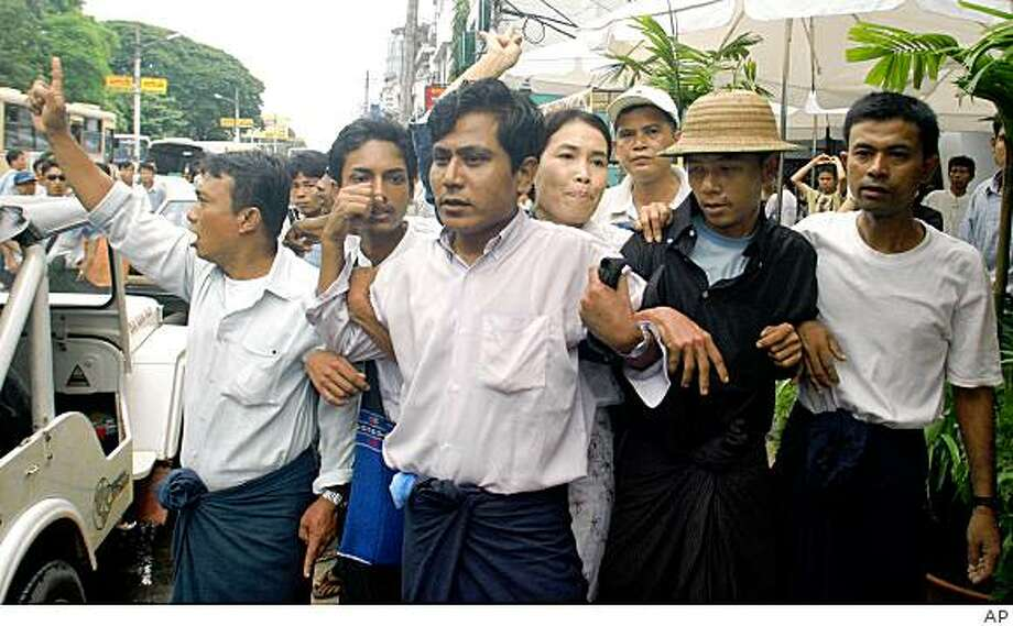**FILE** In a Tuesday, Aug. 28, 2007 file photo, pro-democracy demonstrators link arms to try to protect prominent labor activist Su Su Nway (woman, center) from arrest during a protest in Yangon, Myanmar. Su Su Nway, was sentenced to 12� years in prison Tuesday, Nov. 11, 2008 by courts in military-ruled Myanmar. The court also sentenced some two dozen other activists to harsh prison terms on Tuesday that will keep them behind bars far past a 2010 election.  (AP Photo, File) Photo: AP