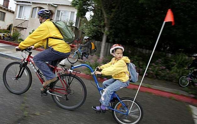 Simon Troll gives neighbor Uma Supatra a ride on his bike as they move through the streets of Berkeley. Simon Toll, his wife Amber Evans and son Kyle Troll are spending a week without using their car in Berkeley, Calif.  They rely on their bicycles for most of their travel Thursday June 3, 2010. Photo: Brant Ward, The Chronicle