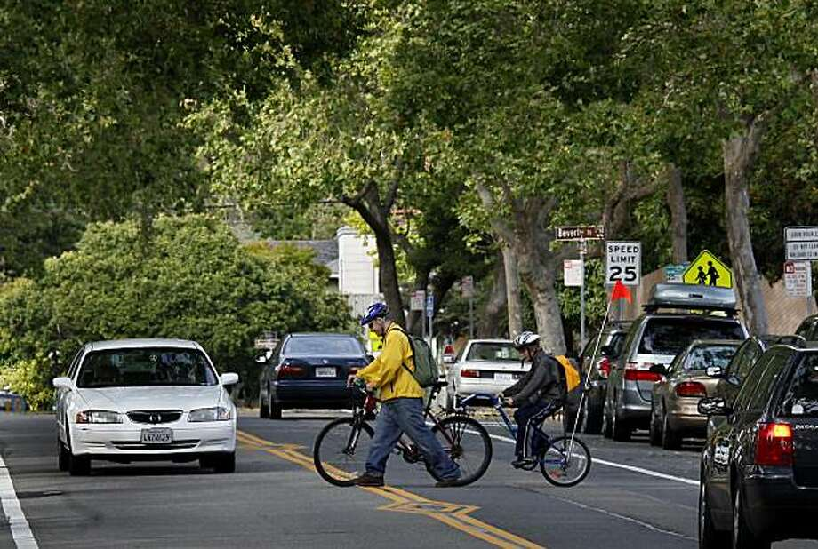 In a file photo, Simon Troll and his son Kyle cross a busy Berkeley street on their way home. Photo: Brant Ward, The Chronicle