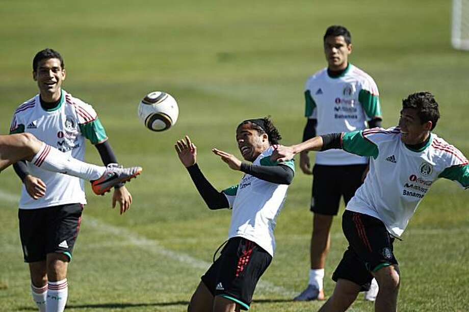 Mexico's national team players Giovani Dos Santos, center, and Efrain Juarez, right, go for the ball as Rafael Marquez, left, and Pablo Barrera, top right, look on during a training session at the Waterstone college in Johannesburg,  Monday, June 7, 2010.Mexico will play in Group A at the soccer World Cup scheduled to start on June 11. Photo: Guillermo Arias, AP