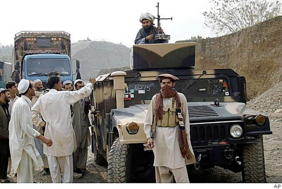 Local Pakistani tribal people stand near an armored car reportedly hijacked by militants in Khyber tribal region of Landikotel, 55 kilometers (34 miles) northwest of Peshawar, Pakistan on Monday Nov. 10, 2008. An officials says security forces are hunting militants who hijacked 13 trucks carrying military vehicles and other supplies for foreign troops in Afghanistan. (AP Photo) Photo: AP