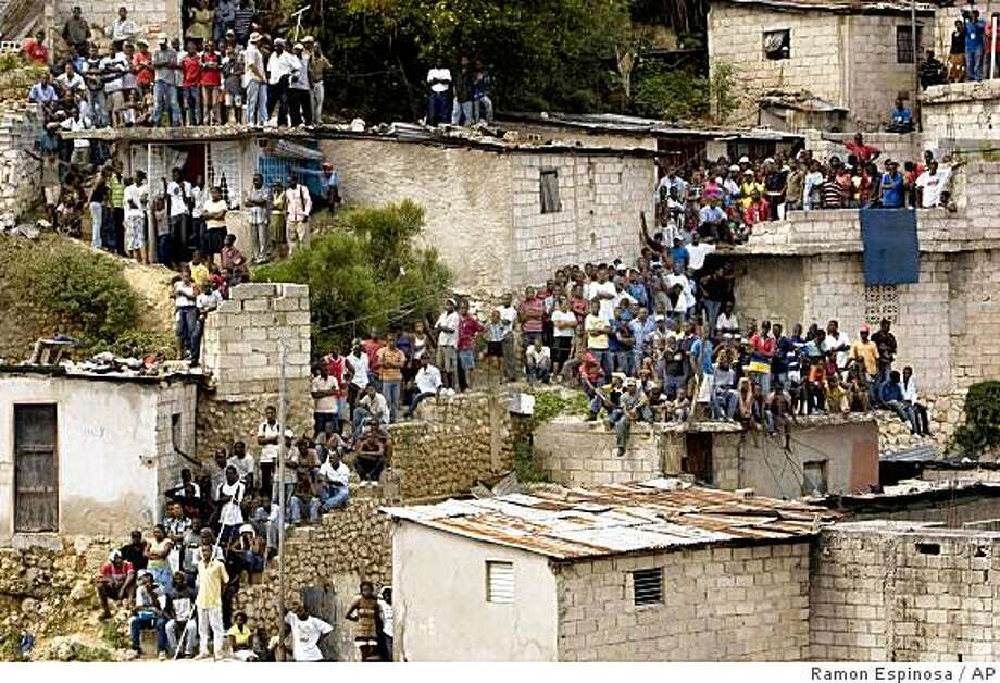 Residents look on as rescue workers search for victims at the 'La Promesse' school after it collapsed in Petionville, Haiti, Saturday, Nov. 8, 2008.  The school, where roughly 500 students crowded into several floors, collapsed Friday during classes killing at least 75 people and injuring many more. (AP Photo/Ramon Espinosa) Photo: Ramon Espinosa, AP