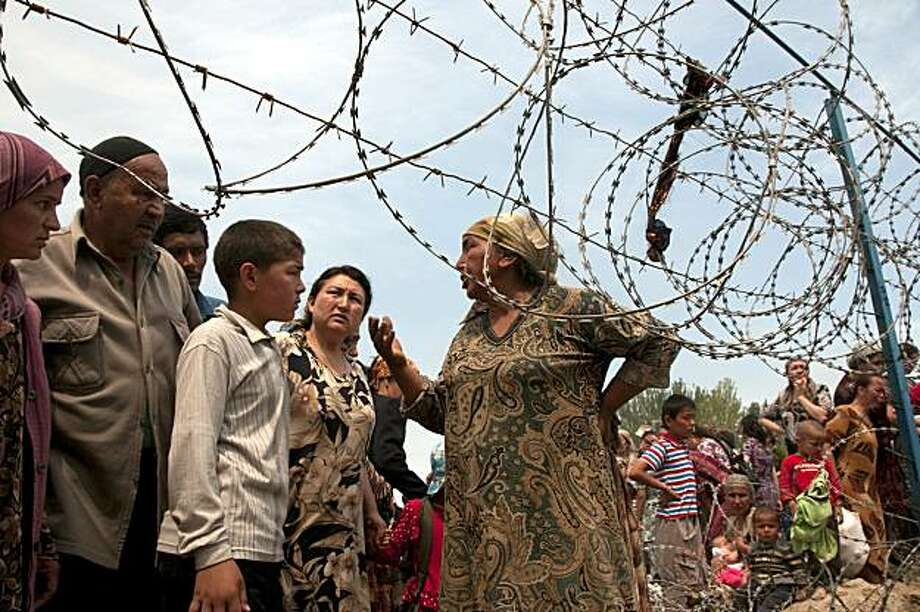 Ethnic Uzbeks gather near the Kyrgyz-Uzbek border in southern Kyrgyzstan, on Saturday, June 12, 2010,  to seek refuge in Uzbekistan from mobs of Kyrgyz men attacking the minority Uzbek community. The country's second-largest city, Osh, slid into chaos Friday when gangs of young Kyrgyz men armed with firearms and metal rods marched on Uzbek neighborhoods and set their homes on fire. Thousands of terrified ethnic Uzbeks were fleeing toward the nearby border with Uzbekistan. Photo: D. Dalton Bennett, AP