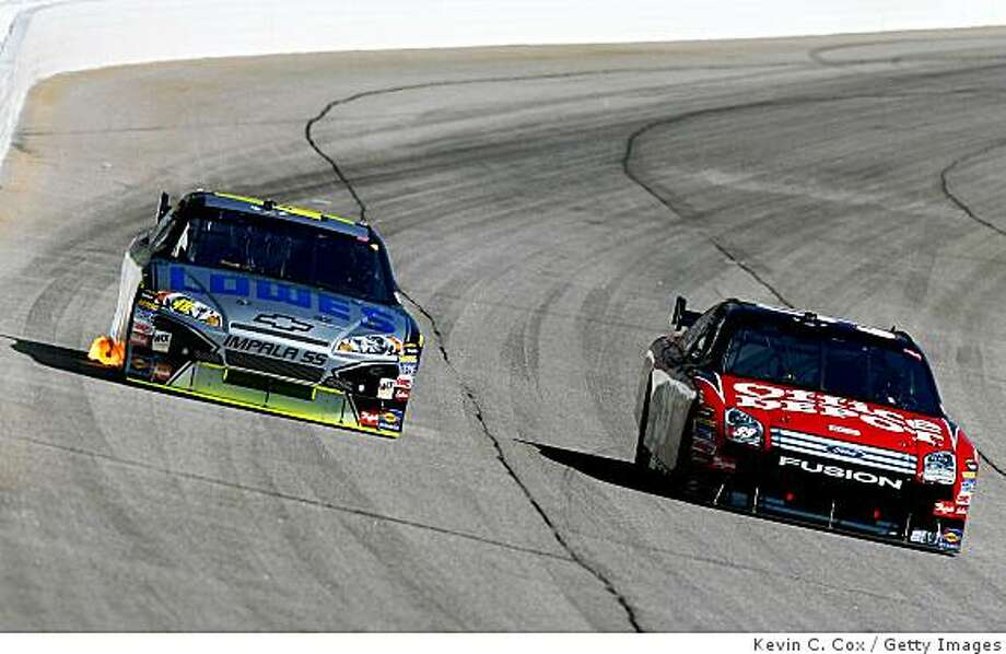 HAMPTON, GA - OCTOBER 26:  Jimmie Johnson, driver of the #48 Lowe's/Kobalt Tools Chevrolet, battles in turn one against Carl Edwards, driver of the #99 Office Depot Ford, during the NASCAR Sprint Cup Series Pep Boys Auto 500 at Atlanta Motor Speedway on October 26, 2008 in Hampton, Georgia.  (Photo by Kevin C. Cox/Getty Images) Photo: Kevin C. Cox, Getty Images
