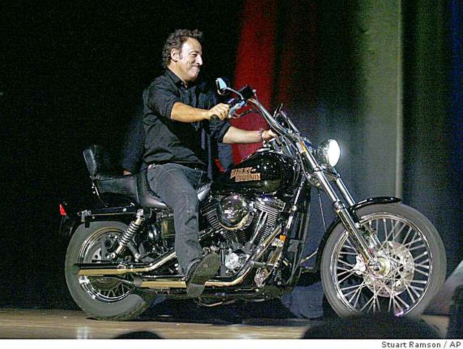 Bruce Springsteen rides his 1994 Harley Davidson Dyna Wide Glide motorcycle on to the stage at the 2nd annual Stand Up For Heroes: A Benefit for the Bob Woodruff Foundation in New York, Wednesday, Nov 5, 2008. The bike was auctioned off with Springsteen's motorcycle jacket for $70,000. (AP Photo/Stuart Ramson) Photo: Stuart Ramson, AP