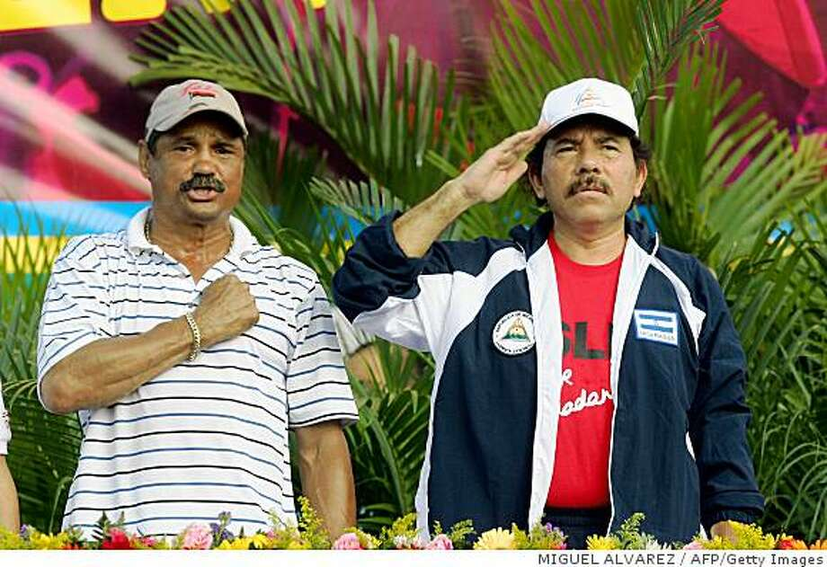 """Managua, NICARAGUA: Nicaragua's President Daniel Ortega (R) and former box world champion and deputy mayor of Managua, Alexis Arguello sing the national anthem, 30 June 2007, in Managua, during the celebration of the 28th anniversary of the """"Tactical Withdrawal"""" to Masaya, a maneuvre of the Sandinista guerrilla in 1979 to defeat the then dictator Anastasio Somoza (1937-1979).   AFP PHOTO/Miguel ALVAREZ (Photo credit should read MIGUEL ALVAREZ/AFP/Getty Images) Photo: MIGUEL ALVAREZ, AFP/Getty Images"""