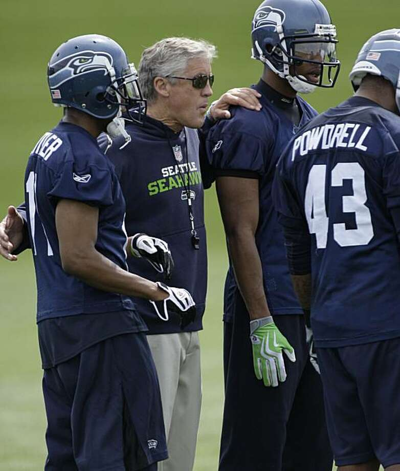 Seattle Seahawks head coach Pete Carroll huddles with his players, including wide receivers Deon Butler, left, Reggie Williams, second from right, and fullback Ryan Powdrell, right, during practice drills, Tuesday, June 8, 2010, as part of an NFL footballorganized team activity in Renton, Wash. Photo: Ted S. Warren, AP