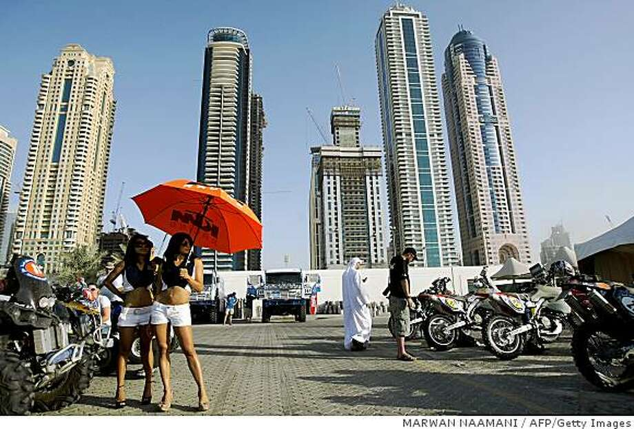 Two cheerleaders of the KTM motorbike company stand under an umbrella at the Dubai Marina prior the start of the final ceremony of the  UAE Desert challenge Competition on October 31, 2008. Qatar Nasser Al-Attiyah driving BMW X3 became the first Arab driver since Qatar?s Saeed Al-Hajri in 1993 to clinch victory in the traditional final round of the FIA World Cup across the remote deserts of the UAE. AFP PHOTO/MARWAN NAAMANI (Photo credit should read MARWAN NAAMANI/AFP/Getty Images) Photo: MARWAN NAAMANI, AFP/Getty Images