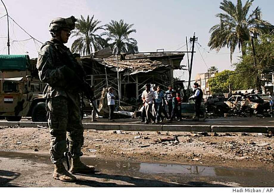 ** CORRECTS DATE **  U.S and Iraqi army soldiers secure the area at the scene were bombs exploded, in Baghdad, Iraq on Monday, Nov. 10, 2008. a suicide bomber struck in a crowd that had gathered where an explosion went off moments earlier, with both blasts killing at least 28 people and wounding 68 others, officials said. (AP Photo/Hadi Mizban) Photo: Hadi Mizban, AP