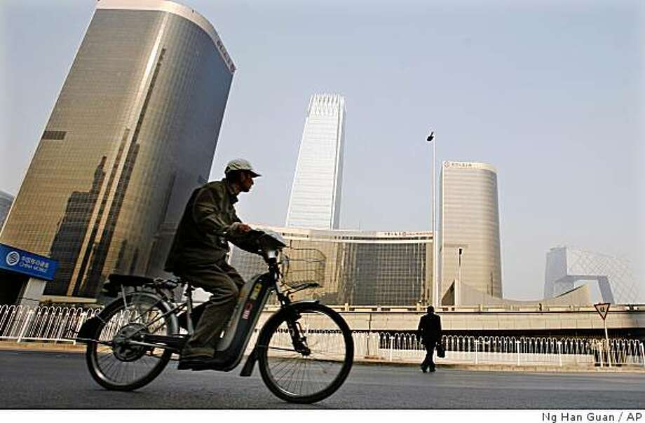 A cyclist and man pass by the central business district in Beijing, China, Monday, Nov. 10, 2008. China announced a 4 trillion yuan ($586 billion) stimulus package Sunday to boost government spending on roads, airports and other infrastructure and bigger subsidies to the poor and farmers. (AP Photo/Ng Han Guan) Photo: Ng Han Guan, AP