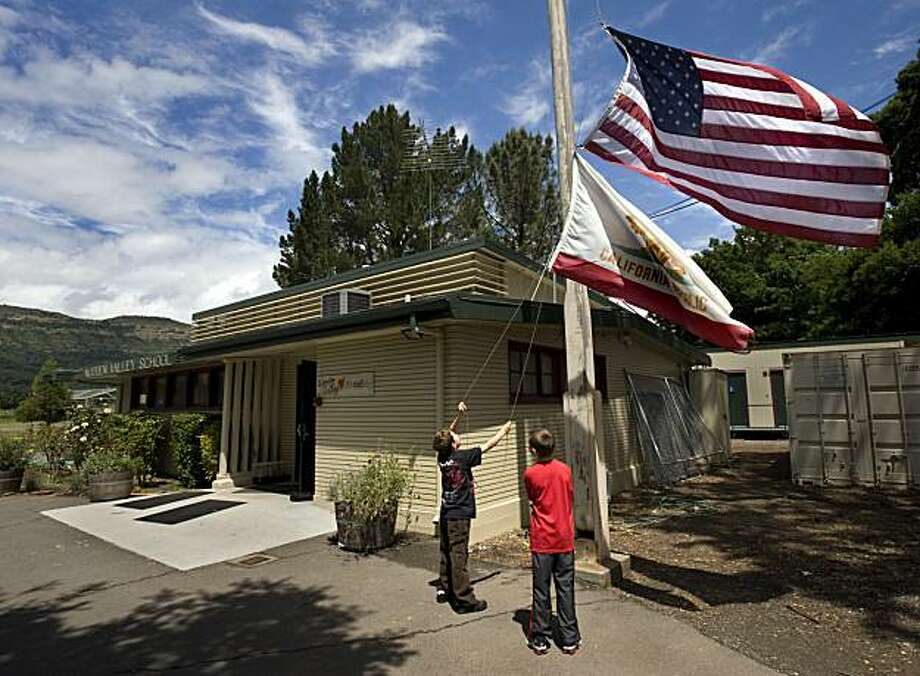 Fourth-grader Peyton Lobosky , 10, left, and fifth-grader Garrett Berger, 11, take down the American and state flags on Wednesday, May 27, 2010 at the Wooden Valley Elementary School in Napa, Calif. The oldest one-room school in California, established in 1853,  is closing its doors for the final time June 10 after its last class of fifth graders graduate. The school is in an isolated farming valley across the Yolo County border in Napa County. After 157 years it has fallen victim to cost cutting measures. (AP Photo/The Sacramento Bee, Randy Pench)  MAGS OUT; TV OUT; NO SALES; MANDATORY CREDIT Photo: Randy Pench, AP