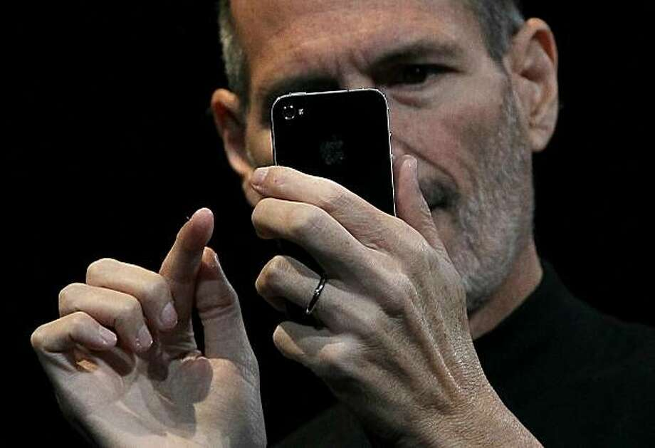 SAN FRANCISCO - JUNE 07:  Apple CEO Steve Jobs demonstrates the new iPhone 4 as he delivers the opening keynote address at the 2010 Apple World Wide Developers conference June 7, 2010 in San Francisco, California. Jobs kicked off the annual WWDC with theofficial unveiling of the latest version of the iPhone. Photo: Justin Sullivan, Getty Images