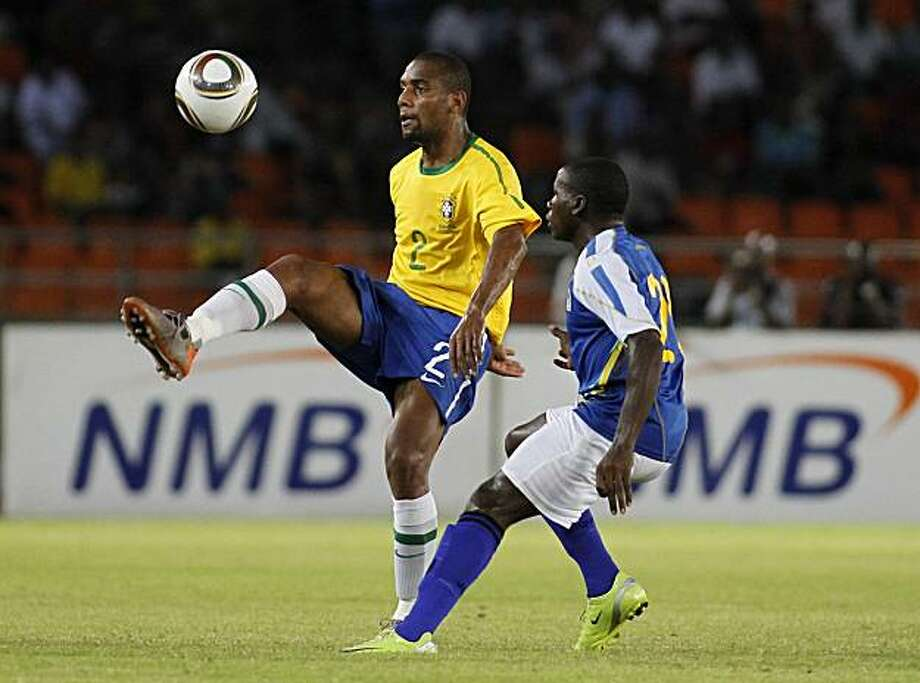 Brazil's Maicon, left, controls the ball as Tanzania's Stephano Mwasika looks on during their friendly soccer match in Dar es Salaam, Tanzania Monday, June 7, 2010. Brazil are preparing for the upcoming World Cup, where they will play in Group G. Photo: Rebecca Blackwell, AP
