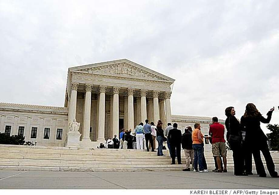 "People wait in line to enter the US Supreme Court on October 6, 2008 in Washington, DC. The US Supreme Court resumes work Monday, weighing a raft of social and environmental issues from light cigarettes to whales, amid uncertainty over the future of the oldest judge on its bench. Forty-nine cases are before the nine seasoned jurists of the highest court in the United States who are to decide within days or weeks whether to delve into the constitutionality of the Bush administration's ""war on terror."" AFP PHOTO/Karen BLEIER (Photo credit should read KAREN BLEIER/AFP/Getty Images) Photo: KAREN BLEIER, AFP/Getty Images"
