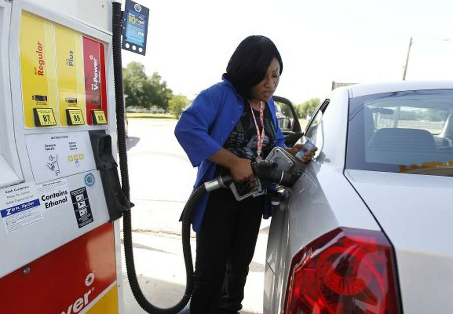Erica Antwi gasses up her car at the Braeswood Shell Station at 8521 Stella Link, Friday, May 13, 2011, in Houston, as people give their opinions about the high cost of gas prices.   ( Karen Warren / Houston Chronicle ) (Karen Warren / Houston Chronicle)