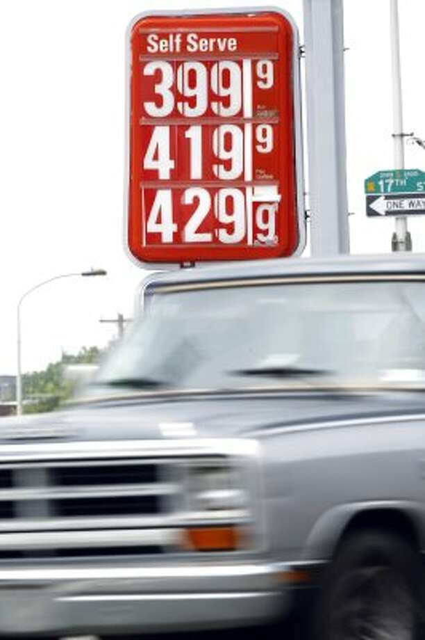A car passes gas prices at a filling station Friday, May 27, 2011, in Philadelphia. For every $10 a household earns, almost a full dollar now goes toward gas _ forcing Americans to rethink what they spend on everything else, including the family vacation. (AP Photo/Matt Rourke) (Matt Rourke / Associated Press)
