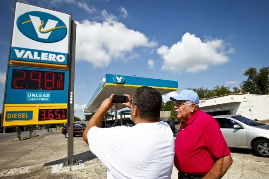 C.R. Martinez (left) takes a photo of the gas price to send to his cousin in California while he brother Ismael (right) looks on after filling their car up with $2.98 gas at a Valero gas station in northwest Houston near W Little York Rd. and T.C. Jester Blvd., Thursday, Sept. 29, 2011.