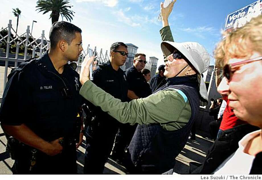 Viriginia Sorgi (with hat) of Oakland reads the Universal Declaration of Human Rights from cards as she stands with other protesters in front of a line of police officers at  the Oakland Mormon Temple to protest the passage of Proposition 8 on Sunday, November 9, 2008 in Oakland, Calif. Photo: Lea Suzuki, The Chronicle