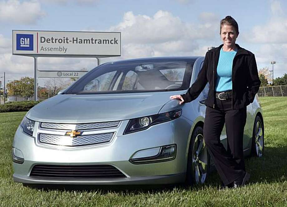 **REMOVES REFERENCE TO DATE**In this undated photo released by General Motors, Detroit-Hamtramck Plant Manager Teri Quigley stands beside a Chevrolet Volt electric vehicle in front of the plant in Detroit. General Motors announced it will invest $336 million in the Detroit-Hamtramck plant to begin production of the Volt electric car, with extended-range capabilities, in 2010. (AP Photo/General Motors, John F. Martin) NO SALES Photo: John F. Martin, AP