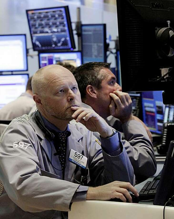 Trader Philip O'Rourke, left, works on the floor of the New York Stock Exchange Monday, June 7, 2010. Photo: Richard Drew, AP