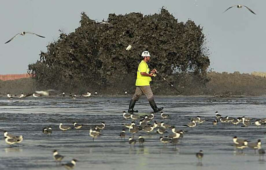 A worker walks past a fountain of sand from a dredge as it is pumped onto East Grand Terre Island, La. to provide a barrier against the Deepwater Horizon oil spill Tuesday, June 8, 2010. Photo: Charlie Riedel, AP