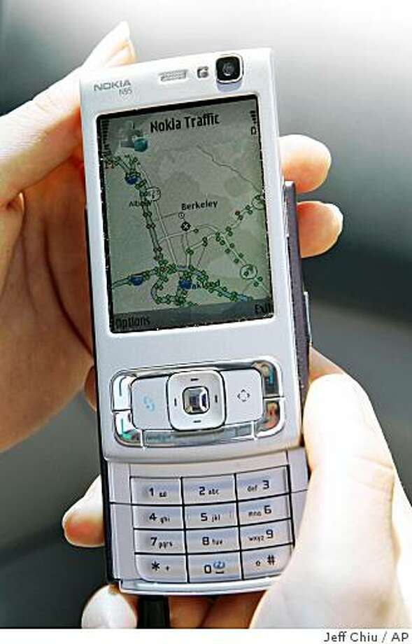 Marcella Gomez, 22, holds up a mobile phone used in the driving portion of the California Center for Innovative Transportation Mobile Millennium field test in Berkeley, Calif., Monday, July 28, 2008. New software for cell phones equipped with a global positioning system will provide commuters with live traffic conditions, tell people how long their commute will take and help them avoid traffic by steering them to less congested roads. (AP Photo/Jeff Chiu) Photo: Jeff Chiu, AP