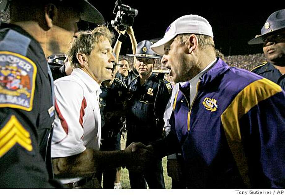 Alabama coach Nick Saban, center left, and LSU coach Les Miles, right, shake hands following Alabama's 27-21 overtime win in Baton Rouge, La., Saturday, Nov. 8, 2008. Photo: Tony Gutierrez, AP