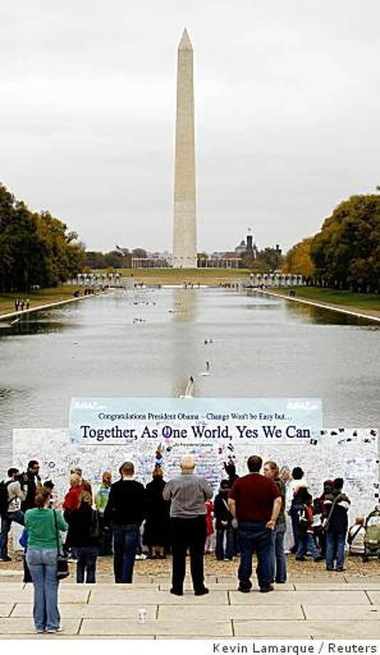 With the Washington Monument towering in the background, people leave messages and read those left by others on a board dedicated to U.S. President-elect Barack Obama near the Lincoln Memorial in Washington November 6, 2008. The board was constructed on Wednesday and will stand all week for people to view and write their thoughts to the new president. REUTERS/Kevin Lamarque   (UNITED STATES) Photo: Kevin Lamarque, Reuters