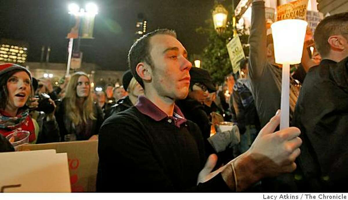 Zachary Davenport holds back his tears as he and hundreds of people gather outside of City Hall for a candlelight vigil in response to the Proposition 8 results in San Francisco, Calif., on Wednesday Nov. 5, 2008.