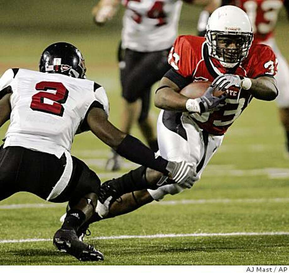 Ball State running back MiQuale Lewis, right, runs past the defense of Northern Illinois cornerback Melvin Rice during the first quarter of an NCAA college football game in Muncie, Ind., Wednesday, Nov. 5, 2008. (AP Photo/AJ Mast) Photo: AJ Mast, AP
