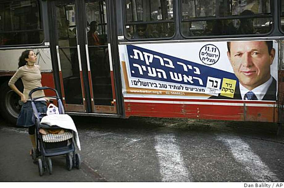 "A girl walks in front of a bus with a campaign sign for Jerusalem Mayoral candidate Nir Barkat Thursday, Oct. 23, 2008. A rabbi, a high-tech investor and a Russian tycoon accused of arms trafficking are vying to be mayor of Jerusalem, the city at the heart of the Israeli-Palestinian conflict. The winner of Tuesday's election takes charge of a troubled piece of land that is being fought over with messianic passion _ and sitting on the fault line of just about every divide Israel has: Arab and Jew, religious and secular, rich and poor, young and old. The fate of the city, claimed as a capital by both Israel and the Palestinians, could prove the deal-breaker in fragile peace talks. Hebrew on sign reads ""Nir Barkat. The Mayor"". (AP Photo/Dan Balilty) Photo: Dan Balilty, AP"