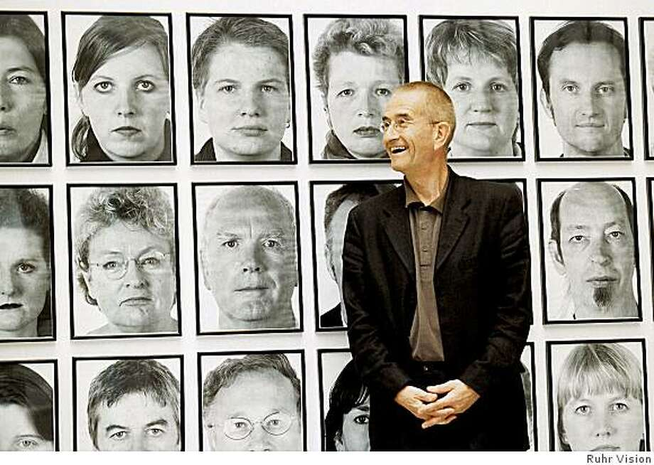 """conceptual artist Jochen Gerz in 2000 standing before photo portraits taken as part of his public project """"The Gift"""" (2000), recreated in 2008 at the San Francisco Museum of Modern Art Photo: Ruhr Vision"""