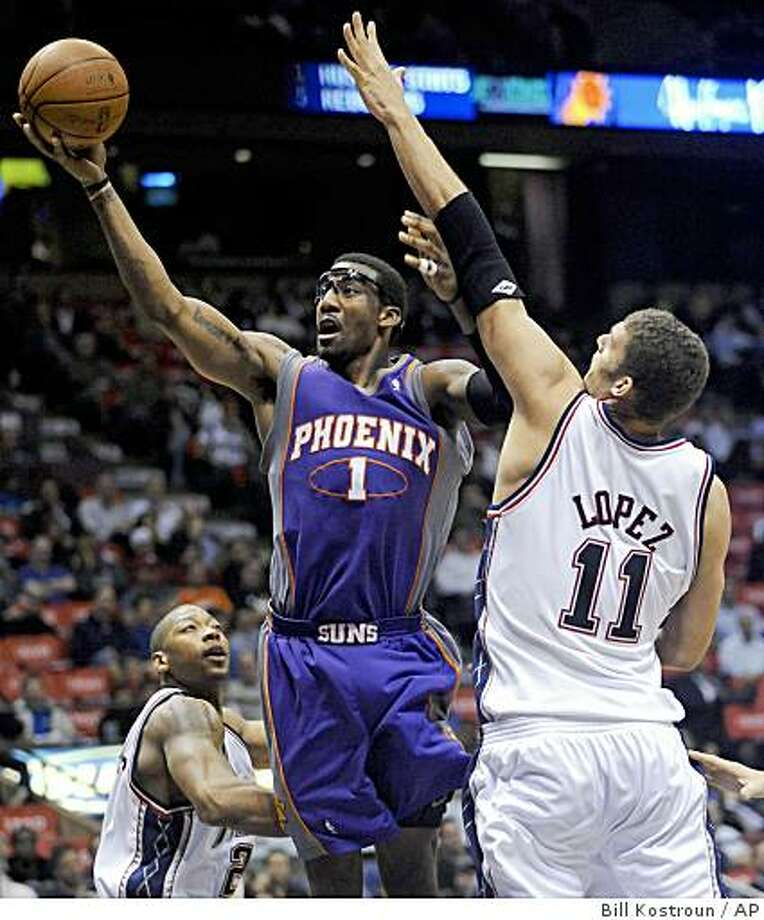 Phoenix Suns' Amare Stoudemire, left, puts up a shot as he gets by New Jersey Nets' Brook Lopez (11) during the third quarter of an NBA basketball game Tuesday, Nov. 4, 2008 in East Rutherford, N.J. The Suns beat the Nets 114-86. (AP Photo/Bill Kostroun) Photo: Bill Kostroun, AP
