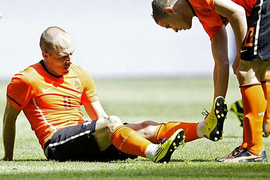 Arjen Robben of The Netherlands grimaces as Ibrahim Afellay, right, holds his leg after suffering a hamstring injury during the friendly soccer match Netherlands versus Hungary at ArenA stadium in Amsterdam, Netherlands, Saturday June 5, 2010. Robben willnot fly out to South Africa with the Dutch team in order to determine the exact nature of his injury in a Dutch hospital. Photo: Peter Dejong, AP