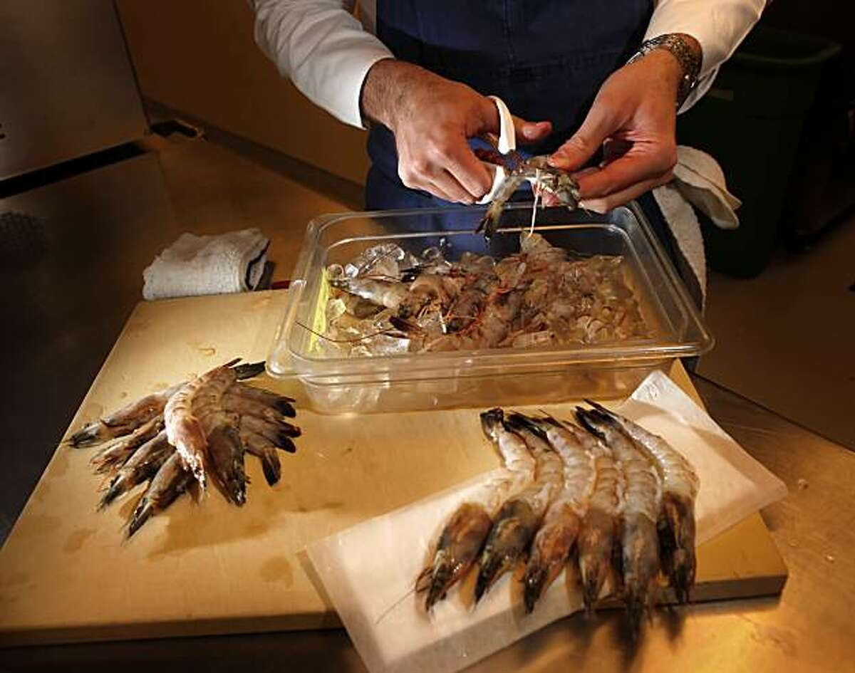 Chef Jason Berthold cleans and prepares shrimp in the kitchen at the RN74 restaurant, Thursday May 27, 2010, San Francisco, Calif. Companies San Francisco based are still using shrimp despite the oil spill of the coast of the Pacific.