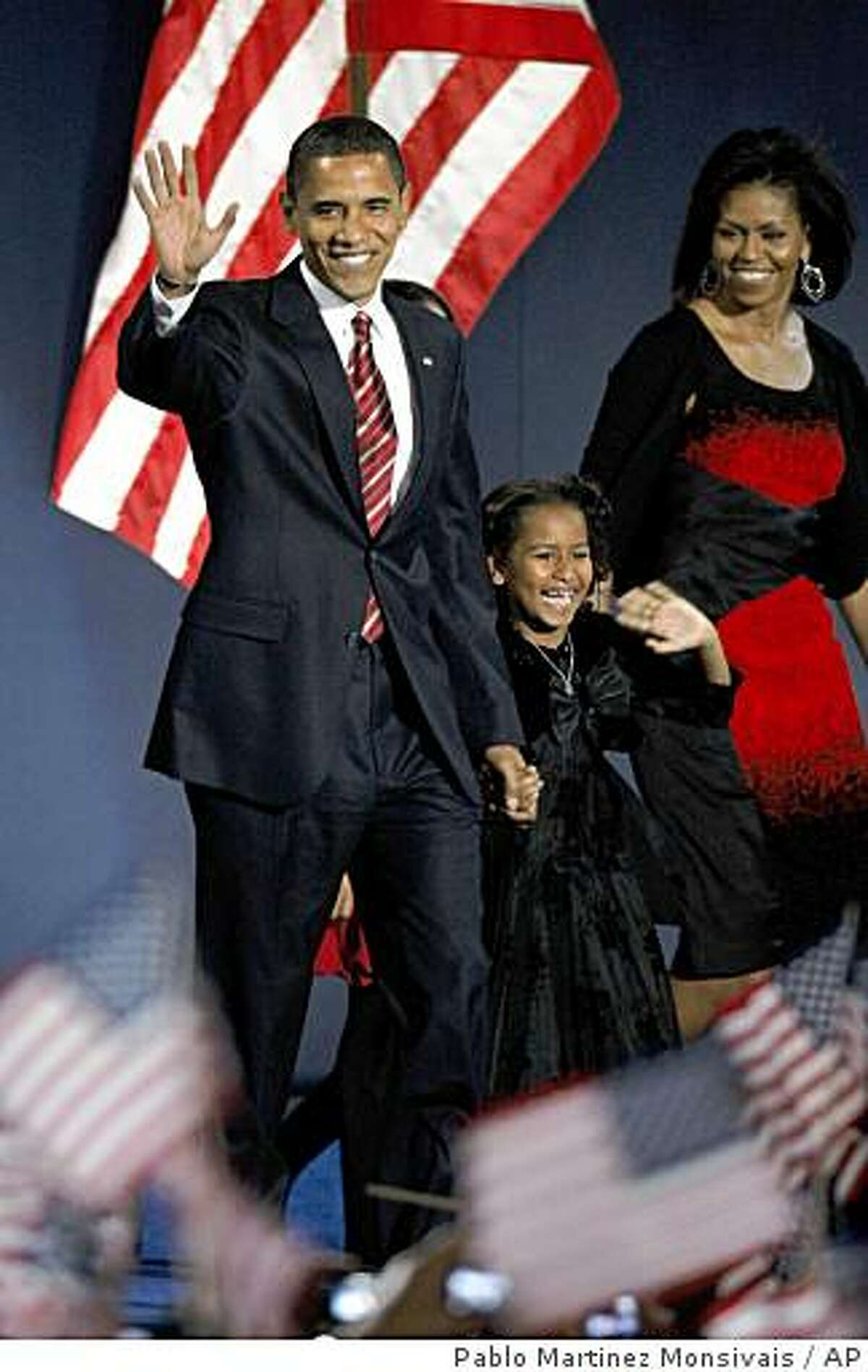 President-elect Barack Obama, his wife Michelle and daughter Sasha, 7, wave as they take the stage at his election night party at Grant Park in Chicago, Tuesday night, Nov. 4, 2008. (AP Photo/Pablo Martinez Monsivais)