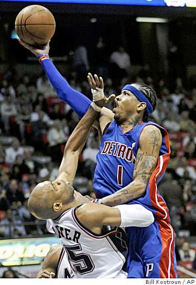 Detroit Pistons' Allen Iverson, right, puts up a shot as he is fouled by New Jersey Nets' Vince Carter during the fourth quarter of an NBA basketball game Friday night, Nov. 7, 2008 in East Rutherford, N.J. Iverson scored 24 points but the Nets beat the Pistons 103-96. (AP Photo/Bill Kostroun) Photo: Bill Kostroun, AP